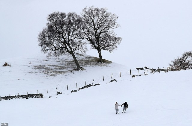 A couple climb a hill whilst sledging near the village of Spittal of Glensheein Perth and Kinross, Scotland, this afternoon