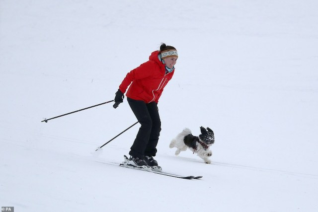 A woman skis on a hill at Spittal of Glenshee in Perth and Kinross, Scotland, while a dog runs alongside her