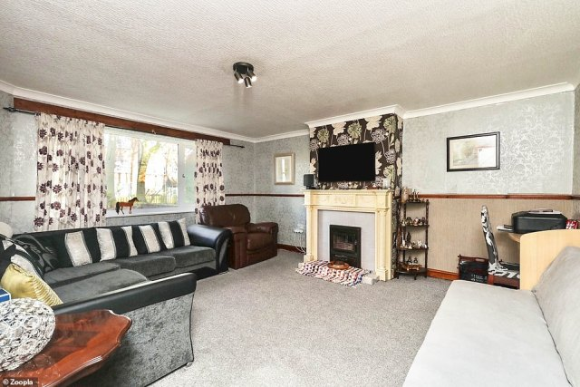 The property has a large living area with a feature fireplace and space for several sofas and armchairs