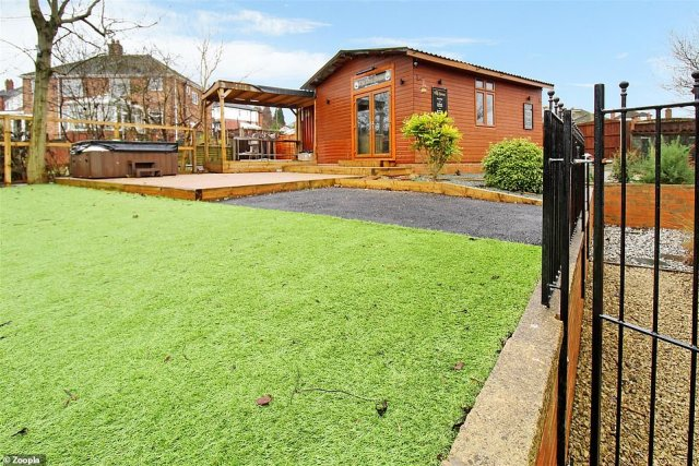 The surprise in the rear garden is a large outbuilding that houses fun and games to escape the pandemic with a hot tub and decking next to it