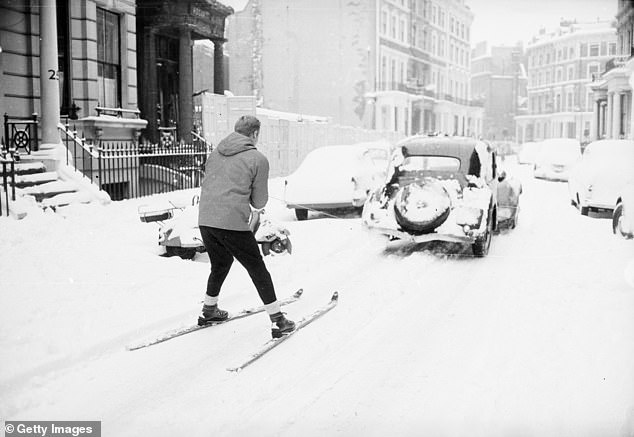 A skier pictured being pulled along behind a car in Earl's Court, London, on December 29, 1962