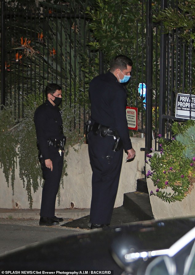 LAPD cops swarmed Marilyn Manson's Hollywood Hills home amid concerns for his safety Wednesday night, as at least 11 women have now come forward and accused the rocker of abuse. Pictured officers at the gates to Manson's home