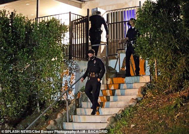 Police later said they were able to make contact with someone and found 'no evidence of any trouble whatsoever' at the property. Officers pictured at a neighbor's door as they tried to make contact with Manson