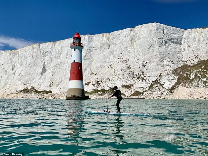 Jordan paddling past the beautiful lighthouse at Beachy Head on the south coast of England