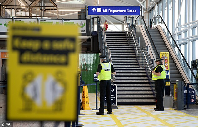 Once in place, arrivals will have to stay in hotels for 11 nights at a cost of up to £1,000 per person. Pictured: Officers at Bristol Airport