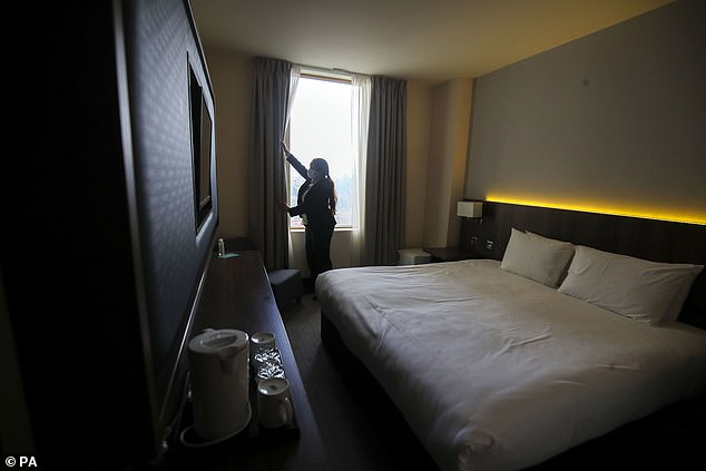 Andreia Neves, guest service manager, prepares a room at the St Giles Hotel in Feltham, west London
