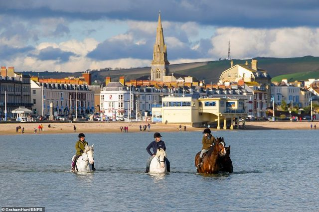 Three horse riders make the most of the warmer weather in Weymouth, Dorset today as the sun draws crowds to the seafront