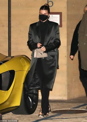 Sofia Richie tailors a chic figure into a black silk coat and jumpsuit as she heads out to dinner