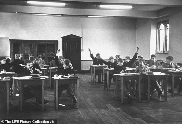 An algebra class raise their hands to show who worked out the problems in 1951