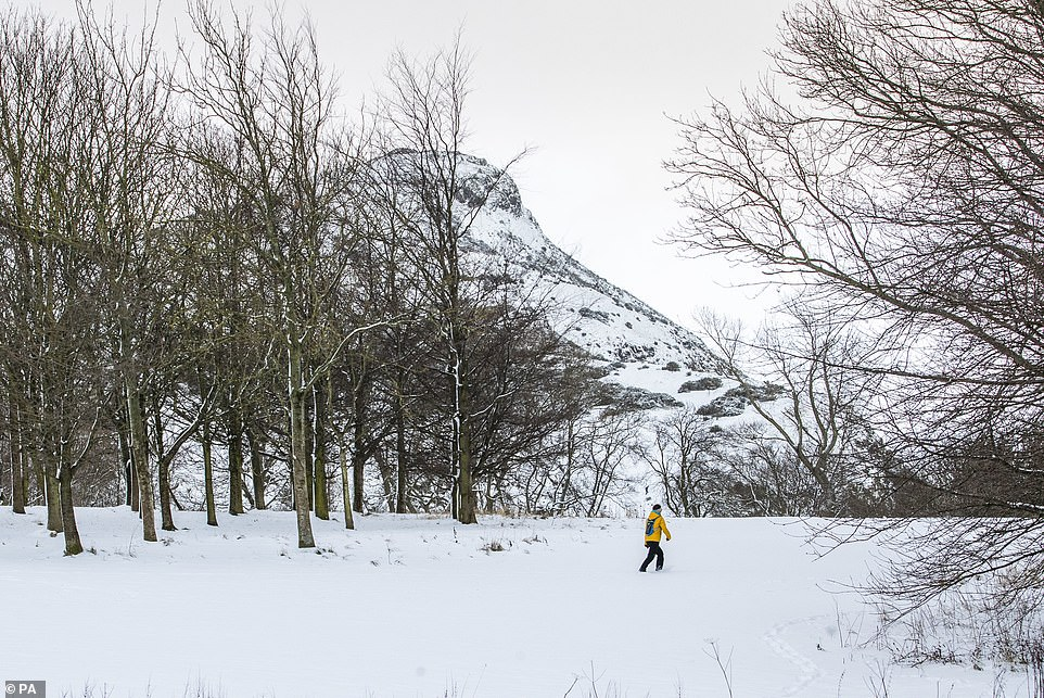 A woman walks through the snow in Holyrood Park, Edinburgh.A Met Office forecast has warned of extreme cold temperatures as most of Scotland is expected to sit below zero Celsius on Wednesday night