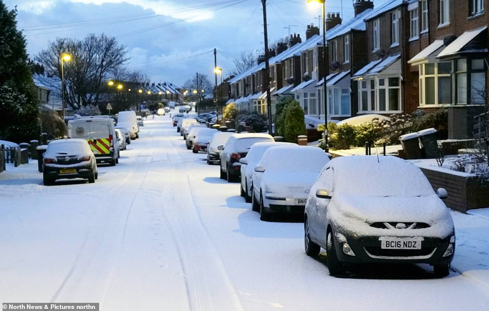 Cars covered in snow on a residential street in Cullercoats, North Tyneside, this morning