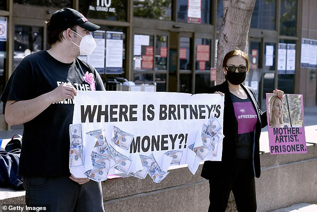Two #FreeBritney supporters hold a sign with the words: 'Where is Britney's money?!