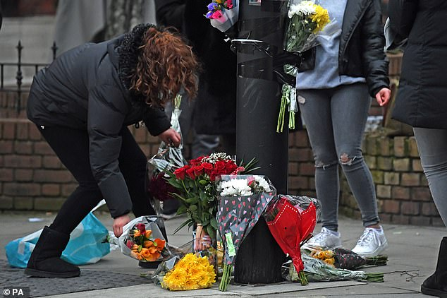 A group of about 50 people were seen near the scene of the stabbing near Parsons Green laying flowers