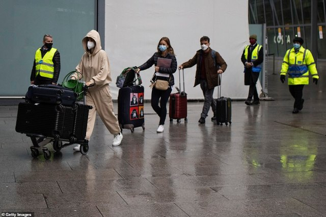 Passengers arriving at Heathrow's Terminal 5 are escorted by security personal to buses this morning on their way to a hotel