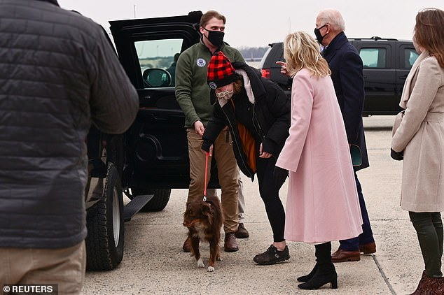 Biden's granddaughter Naomi and her boyfriend Peter Neal manage Naomi's dog - all three flew back from Camp David with President Biden and Jill Biden