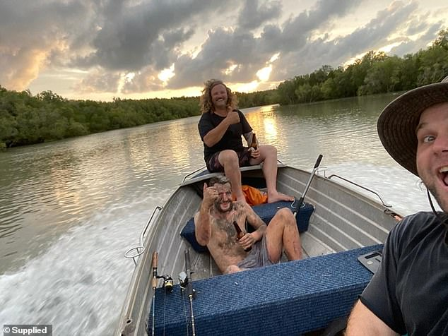 Joiner (centre) and Faust (right) pictured with Voskresensky after finding him in the mangroves. They said his feet were swollen from bites are finding him