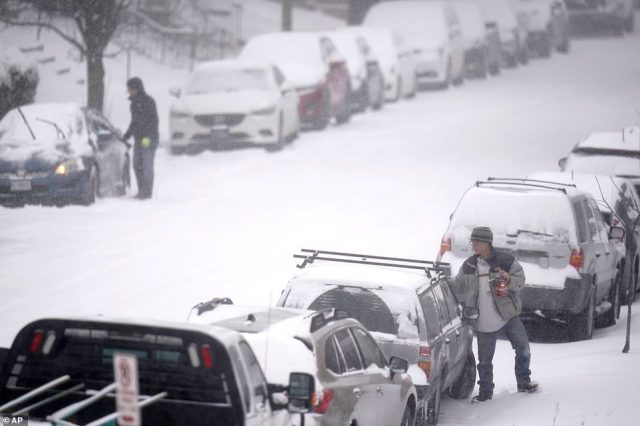 MISSOURI: People clear snow off of cars on Monday in St Louis, Missouri, where the storm brought snow and brutally cold temperatures