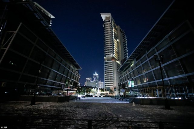 TEXAS:4.38 million people in the Lone Star State are currently without power as of Monday night (pictured:In order to save electricity, the promenade lights and screens are turned off in front of American Airlines Center which was to host the Nashville Predators and the Dallas Stars NHL hockey game)