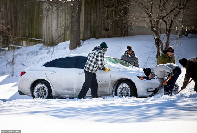 TEXAS: A man shovels snow from under a car stuck on a hill in Austin on Monday morning with the help of friends