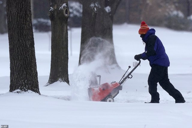 KANSAS:A man clears snow from a driveway in Prairie Village where temperatures are expected to drop to -9 degrees