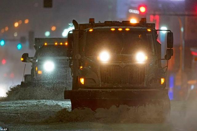 MISSOURI:Snow plows clear a street as temperatures drop below 0 degrees Fahrenheit Monday in Kansas City