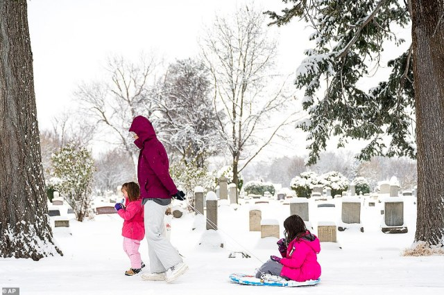 IDAHO:Amy Shoemaker, of Lewiston, Idaho, walks alongside her youngest daughter Vera Shoemaker, 3, and pulls her older daughter, Ella Shoemaker, 6, in a sled as they eat popsicles while passing by the Normal Hill Cemetery, in Lewistone