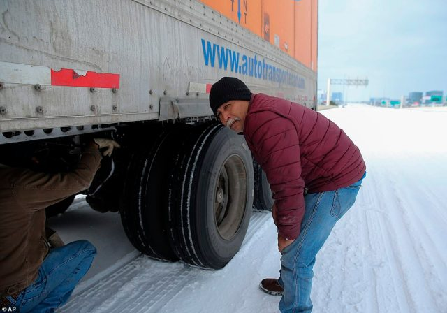 TEXAS:Daniel Del Rio, left, and Robert Barrientos try to fix their 18-wheeler that broke down on Interstate 10 eastbound due to the cold weather in Houston