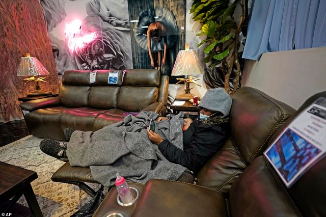 Houston, Texas: The winter storm has resulted in people sleeping in their cars and furniture stores to keep warm amid unprecedented rolling blackouts that have plunged five million into darkness.Natalie Harrell holds her sleeping daughter, Natasha Tripeaux while sitting in a recliner at a Gallery Furniture store