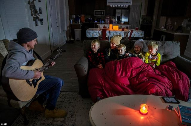 Pflugerville, Texas: Brett Archibad tries to entertain his family as they attempt to stay warm in their home Tuesday