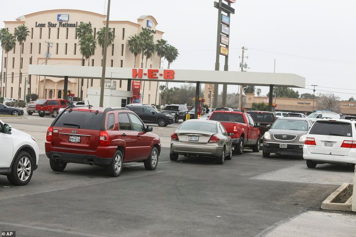 A long line of cars snakes out of the H-E-B gas station and into the supermarket's parking lot Tuesday, Feb. 16, 2021 in Brownsville, Texas