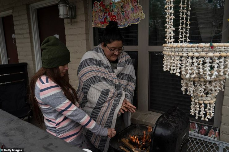 HOUSTON: Karla Perez and Esperanza Gonzalez warm up by a barbecue grill during power outage caused by the winter storm on February 16, 2021 in Houston, Texas