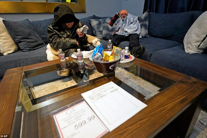 Brett Saint, right, and Joetta Myers sit on a sofa inside a Gallery Furniture store which opened as a shelter Wednesday, Feb. 17, 2021, in Houston