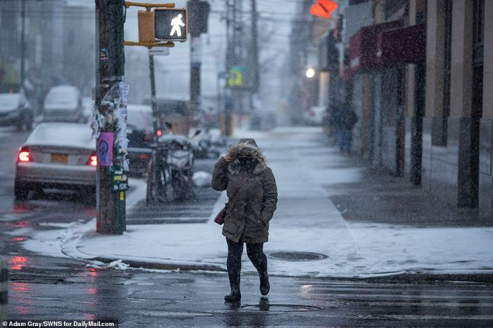 BROOKLYN, NEW YORK: A woman is seen crossing the street in Brooklyn, New York, Thursday morning as snow started to fall