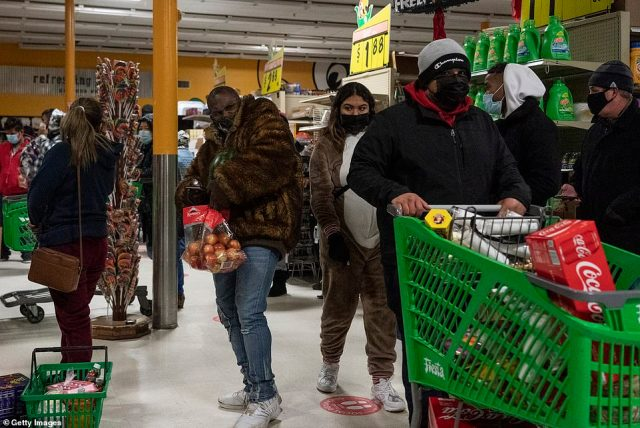 People pictured in aFiesta supermarket in Houston on Tuesday stocking up amid the crisis that has devastated the state