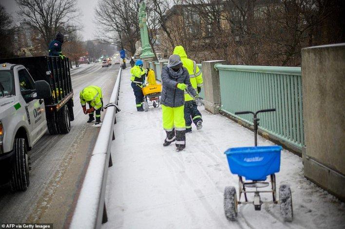 WASHINGTON, DC: City workers spread chemical salt on an icy sidewalk in the Woodley Park neighborhood of Washington, DC, on Thursday