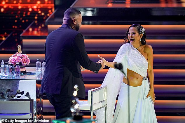 Expecting: After announcing her pregnancy while performing Antes Que Salga El Sol on Thursday night, she displayed her visibly pregnant belly in a stunning midriff-baring gown