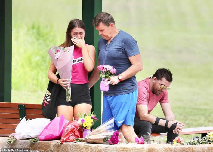 Locals (pictured above) pay their respects at Hannah's Place at Camp Hill on Friday