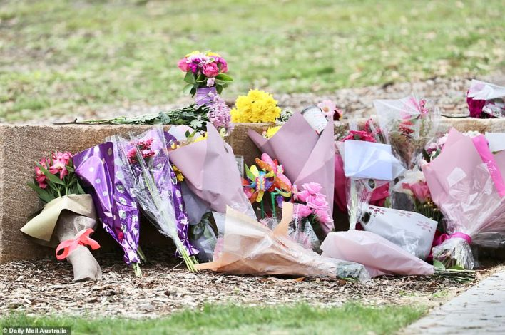 Locals paid their respects (pictured above) with flowers at Camp Hill on Friday