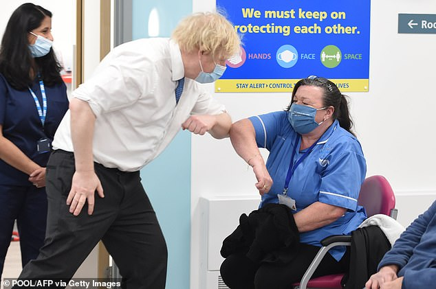 Boris Johnson greets nurse Michelle Bradford at a coronavirus vaccination hub in PPE