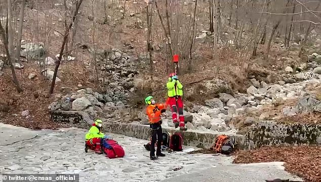 The 33-year-old man was rescued on Thursday after he was spotted lying near a stream in the mountains of Julian Alps in Udine, north-eastern Italy. Pictured, rescuers are airlifted out of the mountains with the injured hiker, who is being wrapped in a sleeping bag (pictured)