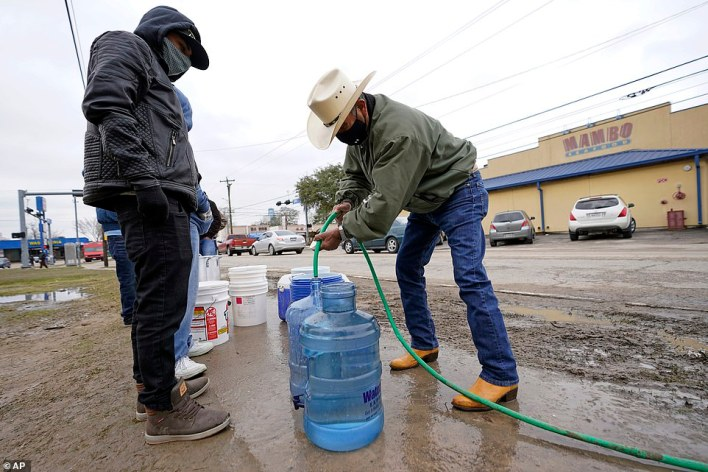 Leovardo Perez (right) fills a water jug using a hose from a public park water spigot Thursday in Houston
