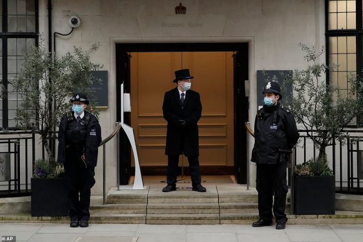 Police officers and a doorman stand outside King Edward VII Hospital in London today, where Prince Philip is being treated