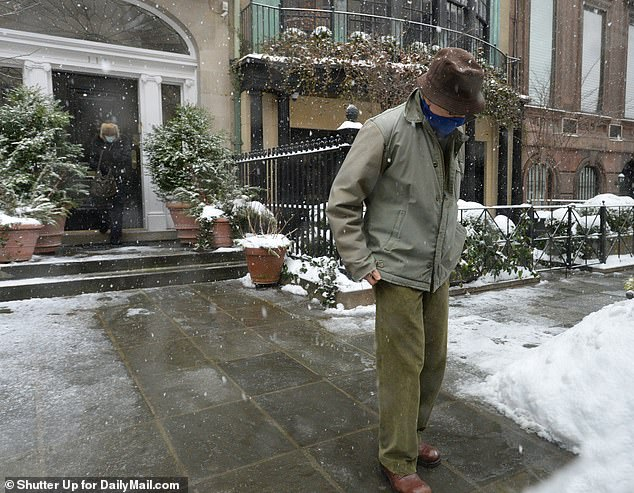 His wife, who donned a medical face mask and fur hat, followed closely behind him as they left their mansion