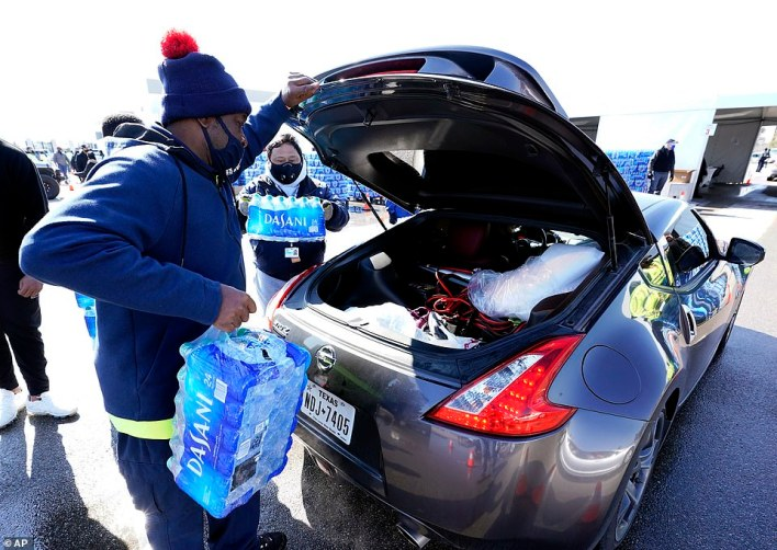 Water is loaded into the trunk of a car at a City of Houston water distribution site on Friday