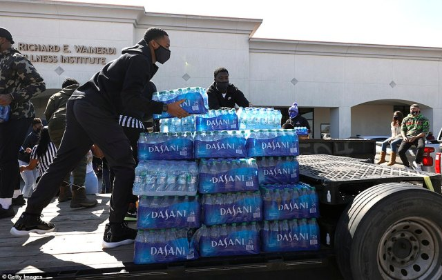 Volunteers stack cases of water during a water distribution event at the Fountain Life Center on Saturday in Houston