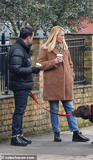 Chatting: They clutched take-out coffees as they strolled around the pretty London street