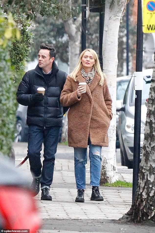 Here they come:Anne-Marie teamed her identical boots with stonewashed ripped jeans, adding a woolly brown coat and checked scarf to the look