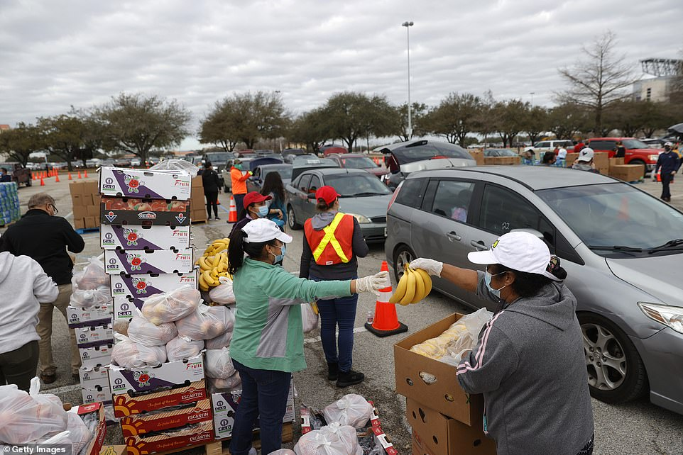 Volunteers prepare to load food into cars during the Houston Food Bank food distribution at NRG Stadium on Sunday.Thousands of people lined up to receive food and water at a mass distribution site for Houston residents who are still without running water and electricity following winter storm Uri