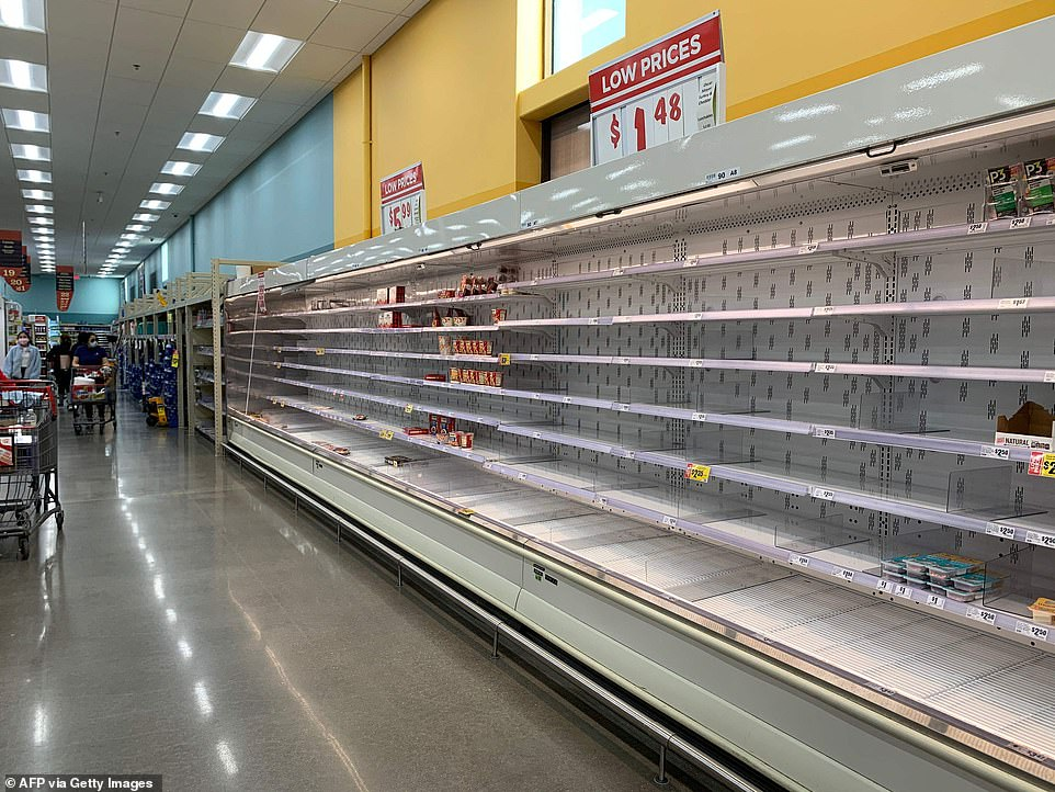 Shoppers are seen wandering next to near empty shelves in a supermarket in Houston, Texas following winter storm Uri