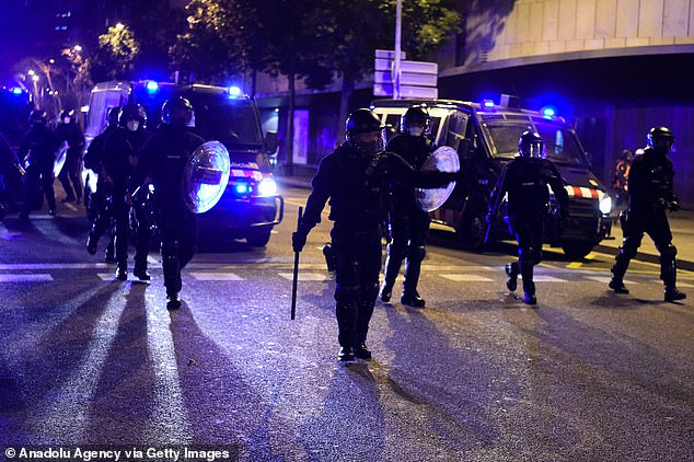 Police move to break up a protest outside the National Police station in Barcelona on Sunday